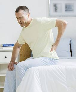 Man in bed with back pain
